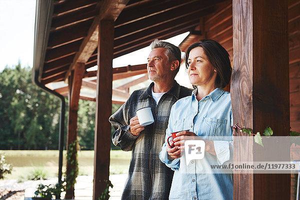 Älteres Paar steht auf der Kabinenveranda  hält Blechbecher und schaut auf die Aussicht