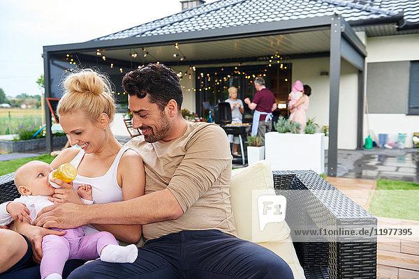Paar füttert Baby-Tochter beim Familienessen auf der Terrasse