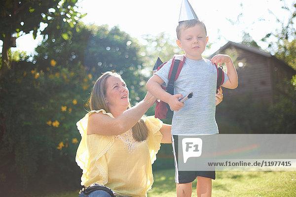 Reife Frau legt ihrem Sohn im Garten einen Raketenkostüm-Rucksack an