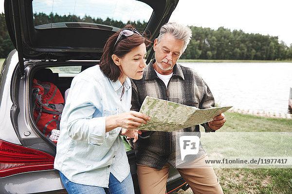 Älteres Ehepaar in ländlicher Umgebung  steht neben dem Auto und schaut auf die Karte