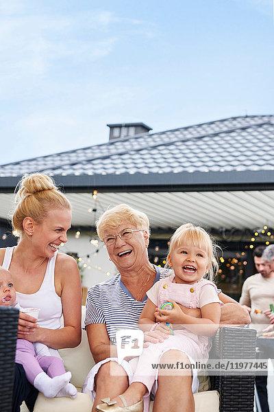 Frauen der dritten Generation mit Kindern auf dem Schoß beim Familienessen auf der Terrasse