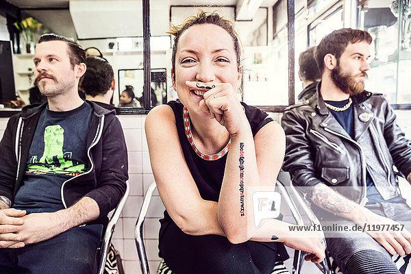 Frau mit Schnurrbarttätowierung am Finger schaut lächelnd in die Kamera