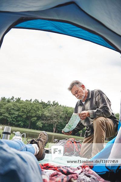 Reife Frau entspannt sich im Zelt  Mann vor dem Zelt  schaut auf die Karte