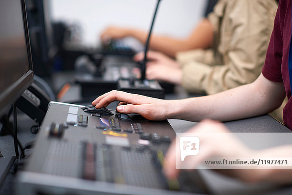 Hands of male and female college students at mixing desk in TV studio