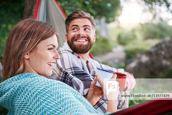 Paar in der Hängematte hält lächelnd Emaillebecher  Krakau  Malopolskie  Polen  Europa