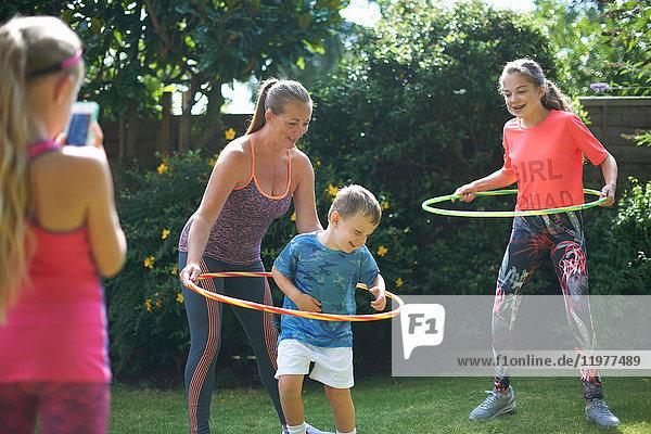 Mädchen fotografiert Mutter und Geschwister beim Hupen im Garten