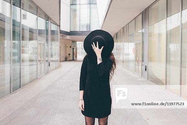Porträt einer jungen Frau in städtischer Umgebung  Gesicht mit Hut bedeckt Porträt einer jungen Frau in städtischer Umgebung, Gesicht mit Hut bedeckt