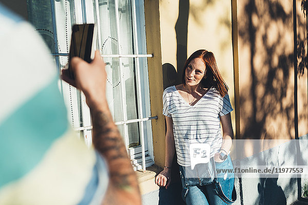 Over shoulder view of man photographing girlfriend leaning against house