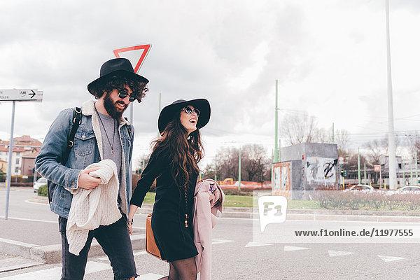 Junges Paar im Freien  überquert Straße  hält Hände  lacht