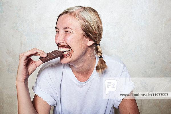 Frau isst eine Tafel Schokolade  Schokolade um den Mund  lacht