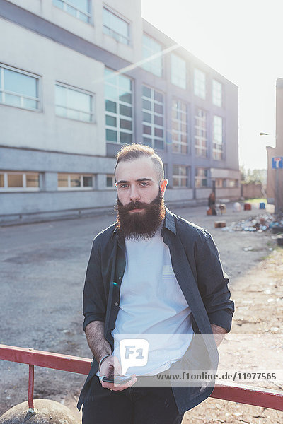 Porträt eines bärtigen Mannes  der ein Smartphone hält und in die Kamera schaut