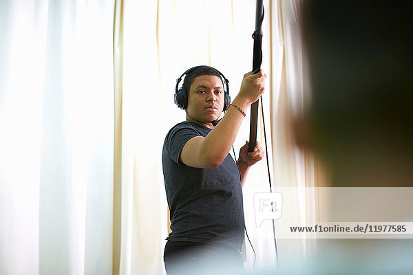 Young male college student recording in TV studio