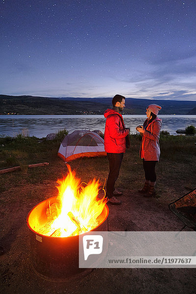 Couple standing near tent and campfire. at dusk  drinking hot drinks