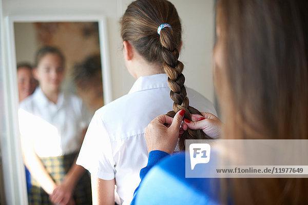 Über-Schulter-Ansicht der Mutter  die der Tochter einer Teenager-Schülerin die Haare flechtet