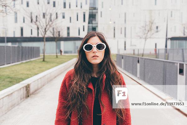 Porträt einer jungen Frau mit Sonnenbrille  stehend in städtischer Umgebung