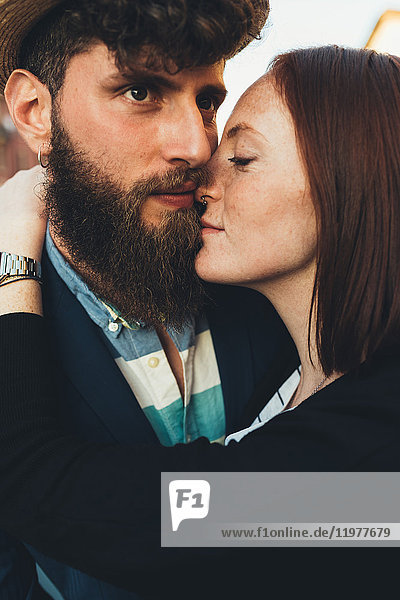 Head and shoulder shot of hipster couple embracing