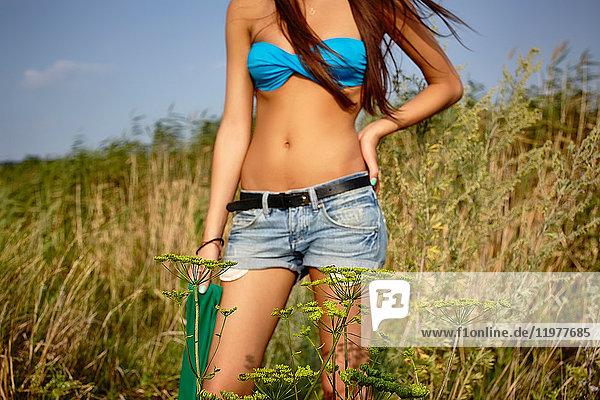 Mittelteil einer jungen Frau in Shorts und Bikinioberteil in langem Gras