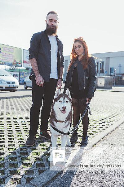 Porträt eines Paares mit Hund  das in die Kamera schaut