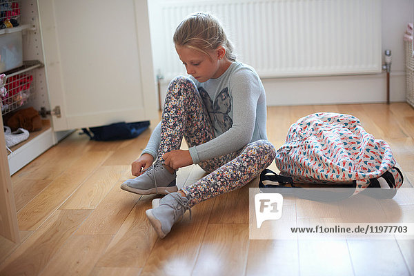 Girl sitting on bedroom floor tying booty laces