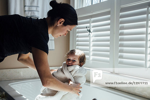 Mother removing daughter from bathtub wrapped in towel