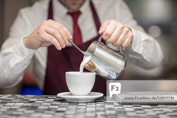 Waiter in restaurant  pouring milk into coffee cup  mid section