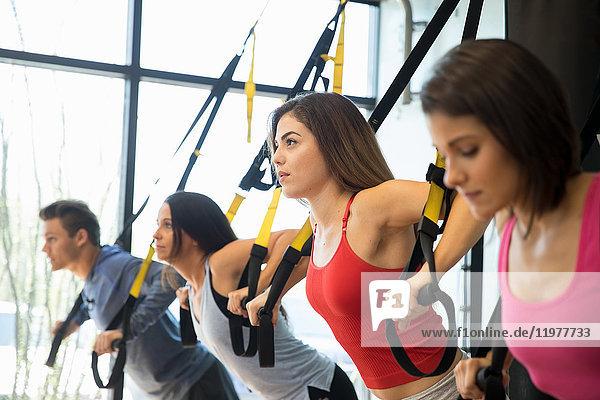 Freunde trainieren mit Widerstandsband im Fitnessstudio