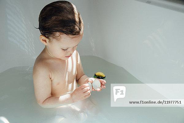 Girl in bath playing with bath toy