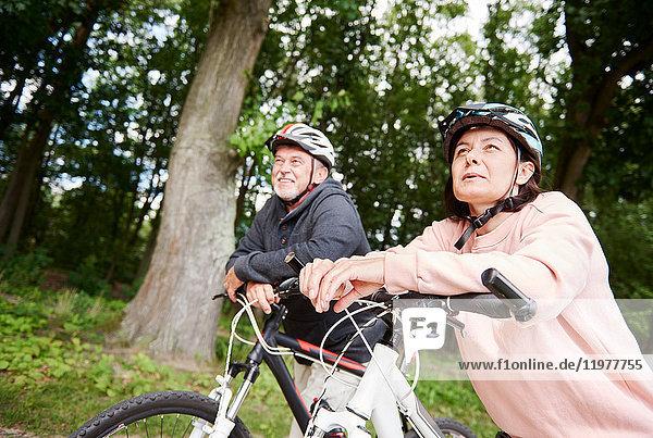 Ein erwachsenes Paar  das mit Fahrrädern den ländlichen Weg entlang fährt und die Aussicht betrachtet