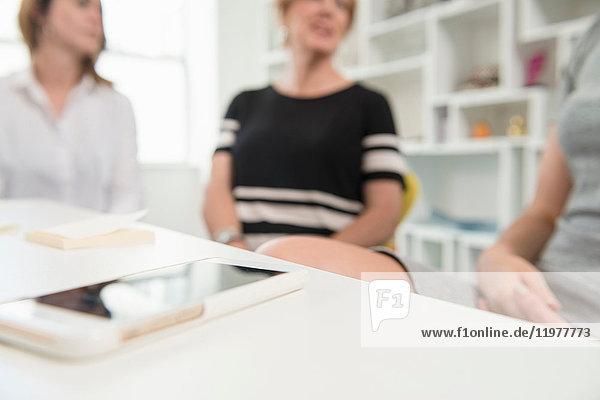 Frauen bei Geschäftsbesprechung  Mobiltelefon im Vordergrund