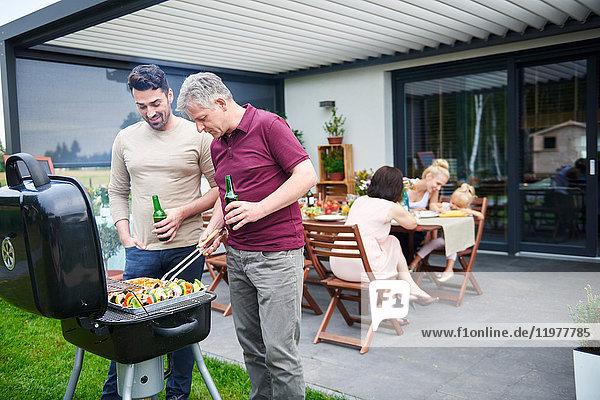 Reife und mittel-erwachsene Männer grillen beim Familienmittagessen auf der Terrasse
