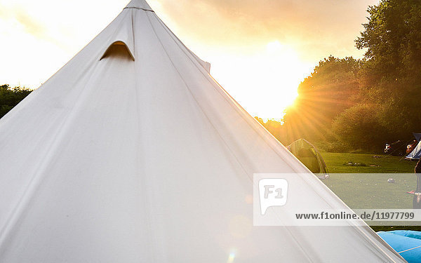 Weißes Zelt auf dem Campingplatz bei Sonnenuntergang