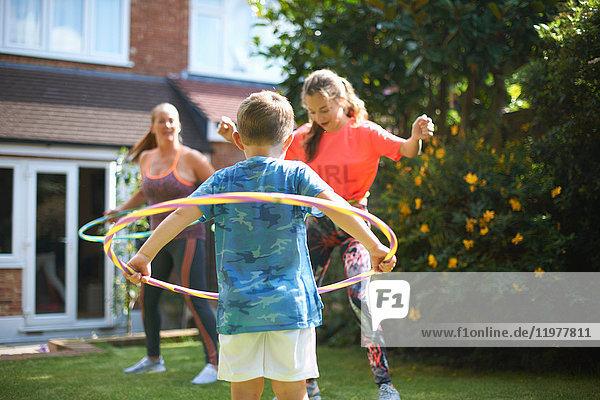 Reife Frau mit Sohn und jugendlicher Tochter hula hopping im Garten