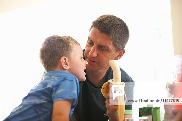 Junge und Vater teilen sich frische Bananen in der Küche