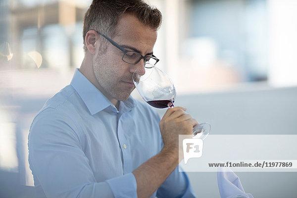 Diner in restaurant smelling wine in wineglass