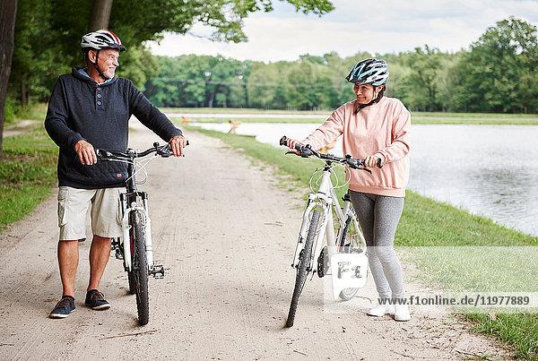 Ein erwachsenes Paar  das mit Fahrrädern den ländlichen Weg entlang fährt und lächelt