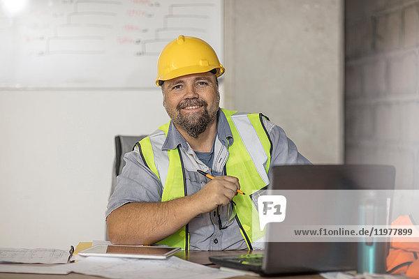 Bauarbeiter mit Laptop am Schreibtisch