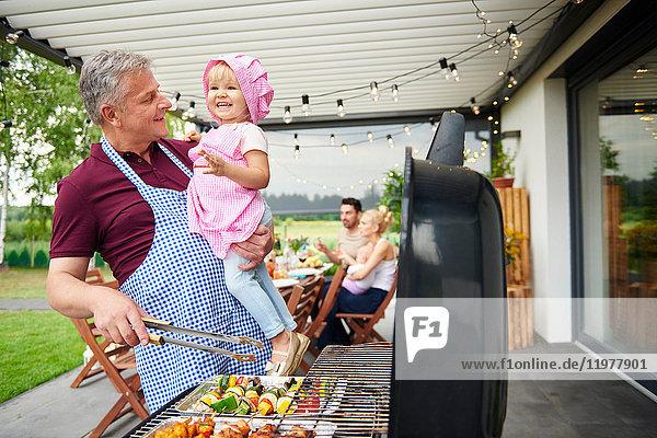 Erwachsener Mann trägt Kleinkind-Enkelin beim Familienessen auf der Terrasse grillen