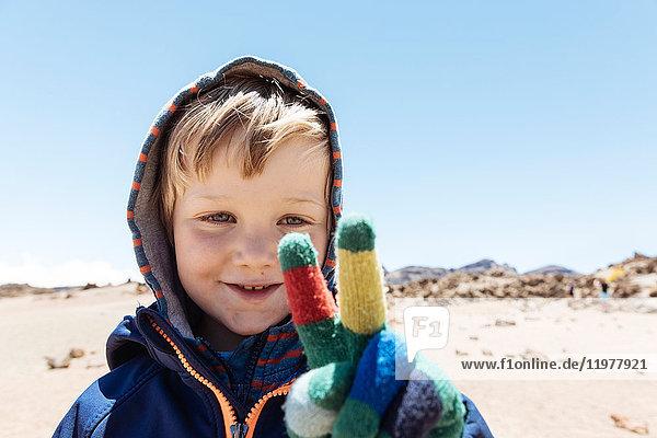 Porträt eines süßen Jungen  der mit Handschuhen ein Friedenszeichen am Teide setzt  Teneriffa  Kanarische Inseln