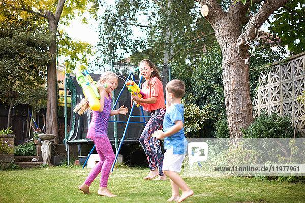 Junge und seine Schwestern bei einer Wasserpistolenschlacht im Garten
