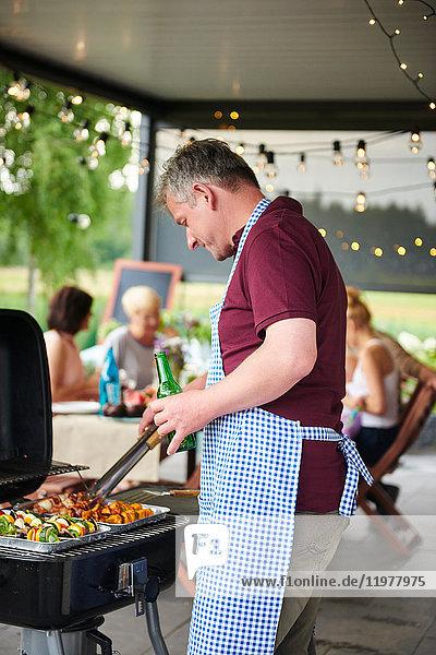 Erwachsener Mann grillt beim Familienessen auf der Terrasse
