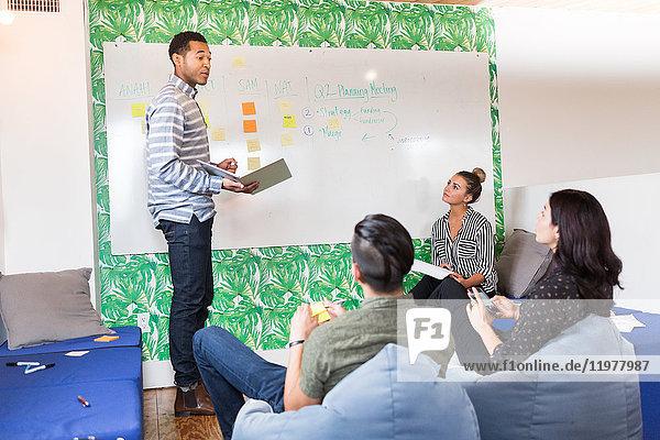 Junger Geschäftsmann hält Laptop-Präsentation im kreativen Sitzungsraum