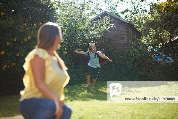 Reife Frau beobachtet Sohn im Pilotenkostüm beim Laufen im Garten
