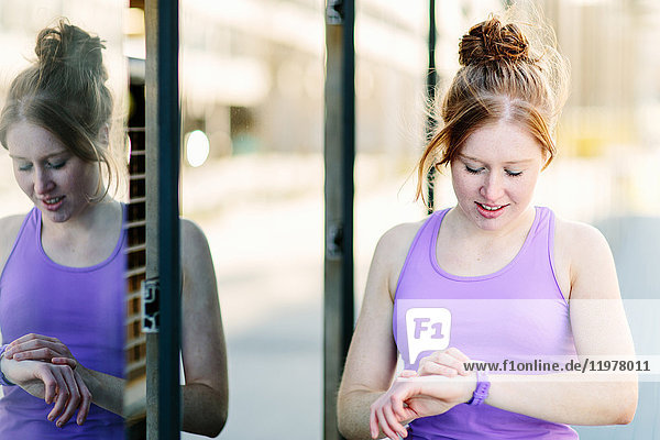 Junge Läuferin betrachtet Smartwatch auf dem Bürgersteig der Stadt
