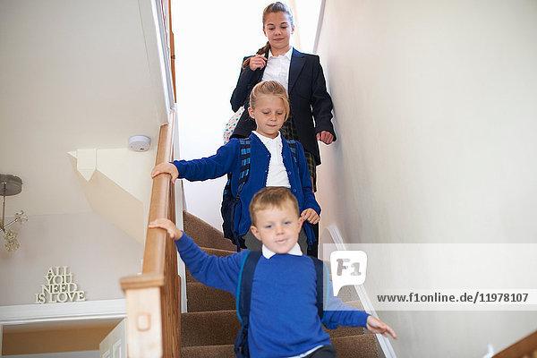Teenager-Schülerin mit Schwester und Bruder in Uniform zieht die Treppe hinunter