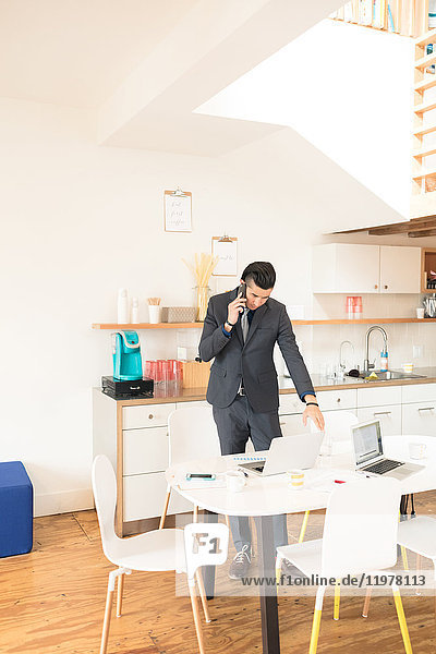 Young businessman making smartphone call at office table