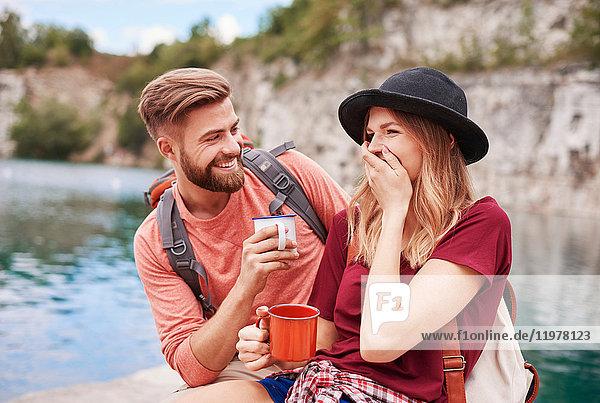 Couple by water holding enamel mugs smiling  Krakow  Malopolskie  Poland  Europe