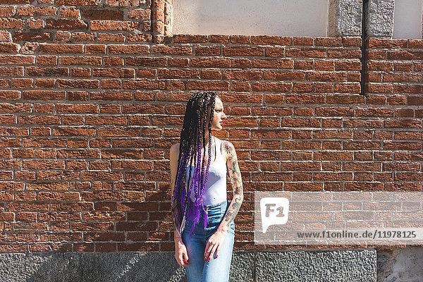 Frau steht neben roter Ziegelmauer