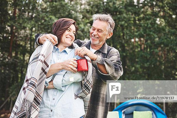 Ein erwachsenes Paar steht neben dem Zelt  der Mann legt der Frau eine Decke um die Schultern