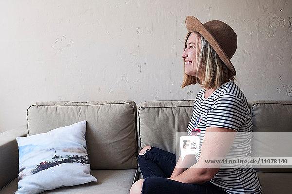 Frau auf Sofa sitzend  lächelnd  Seitenansicht