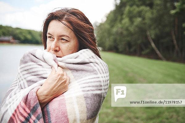 Reife Frau in ländlicher Umgebung  in eine Decke gehüllt